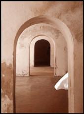 Affiche représentant un chemin de plusieurs passage portes dans des mures de pierre de couleur marron.