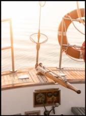 Affiche montrant un magnifique coucher de soleil depuis l'arrière d'un voilier.