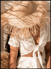 Affiche d'une femme habillée en blanc portant un chapeau de paille au soleil.