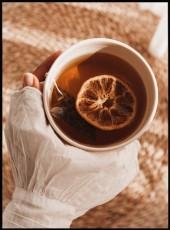 Affiche d'une tasse thé tenue dans une main avec à l'intérieur une rondelle d'orange.