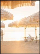 Poster our affiche d'un coucher de soleil sur une plage remplie de parasol en paille.