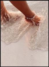 Photographie de pieds féminin marchant dans l'eau.