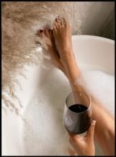 Femme prenant un bain avec un verre de vain dans la baignoire.
