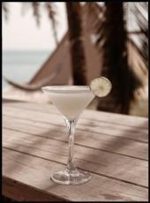 Affiche d'un cocktail posé sur une table en bord de mer.