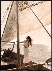 Femme vêtue de blanc debout sur un bateau au milieu de la mer.