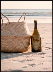 Photographie d'une bouteille de champagne et d'un panier osier sur la plage.