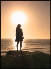 Photographie d'une femme debout sur une falaise regardant le ciel durant un coucher de soleil.