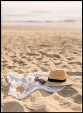 Photographie d'un chapeau, d'une paire de lunettes et de coquillages dans le sable