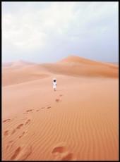 Photographie d'une femme vêtue de blanc marchant dans le désert.