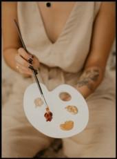 Photographie d'une artiste tenant un pinceau et une palette de peinture aux tons chauds beige, rouille, ocre.