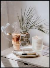Photographie d'un meuble où sont posés une bougie et de l'encens qui brûlent, un livre, une plante et un chocolat chaud.