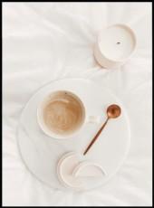 Photographie d'une tasse de café et sa cuillère sur une assiette et d'une bougie posée sur des draps blancs.