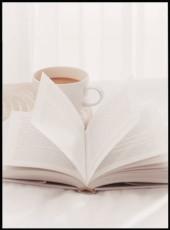 Photographie d'un livre ouvert sur des draps blancs accompagné d'une tasse de café en porcelaine.