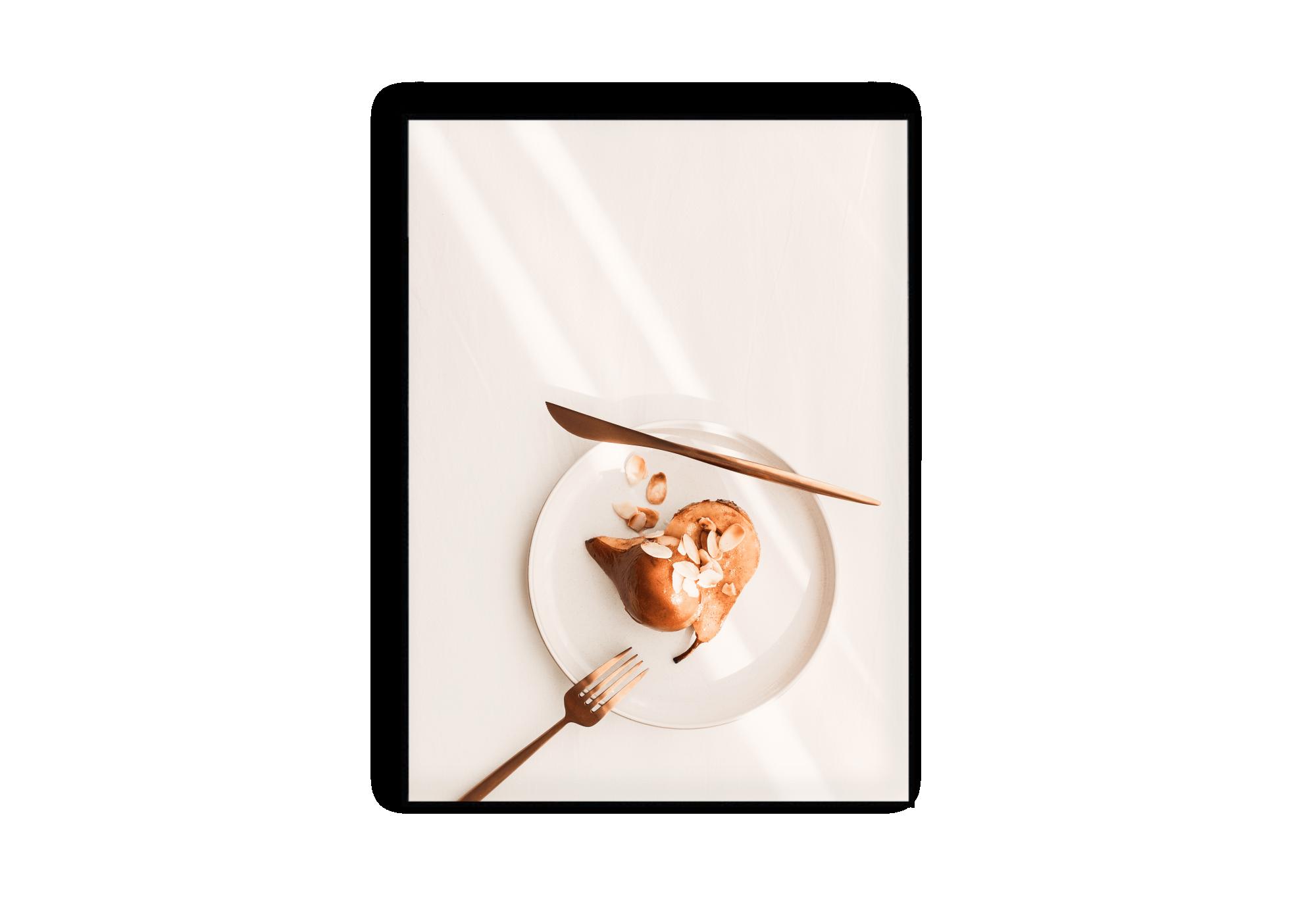 Photographie d'une assiette contenant une poire aux amandes éffilées coupée en deux. Une fourchette et un couteau couleur cuivre sont disposés autour de l'assiette blanche.